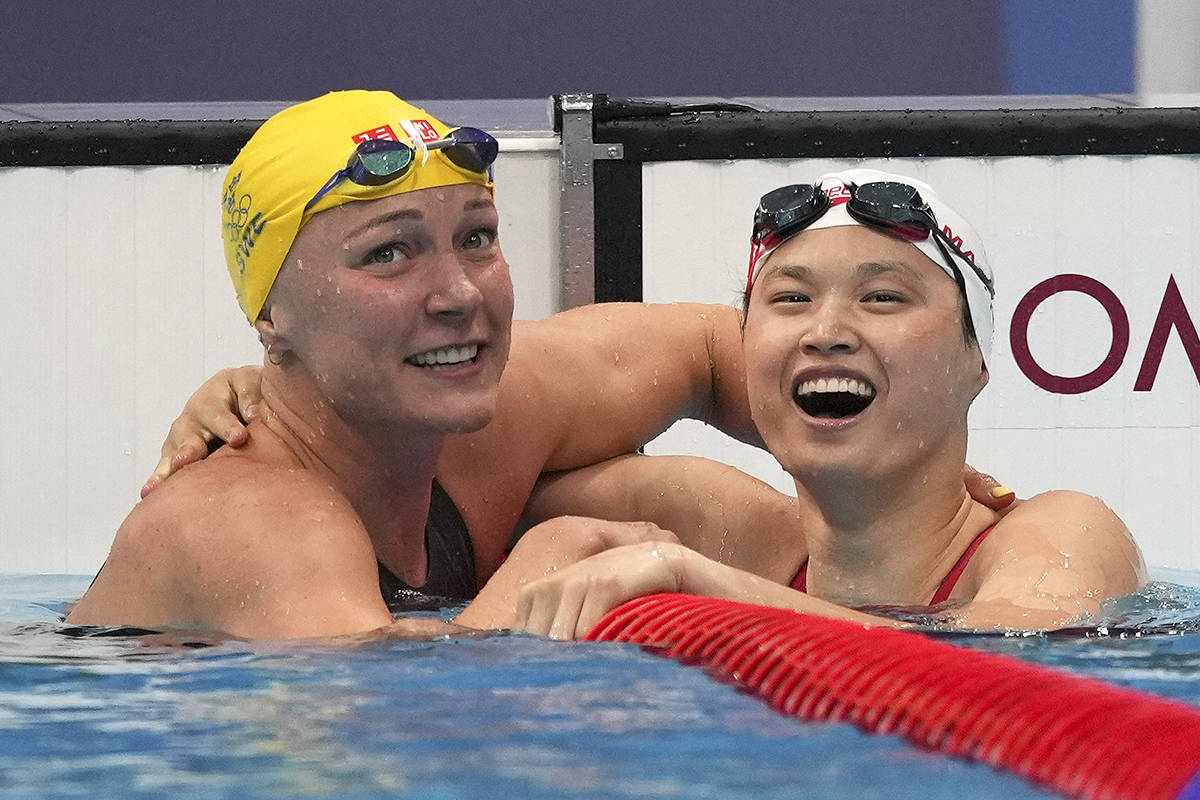 Margaret Mac Neil, right, of Canada, is congratulated by Sarah Sjoestroem of Sweden103 after winning the final of the women's 100-metre butterfly at the 2020 Summer Olympics, Monday, July 26, 2021, in Tokyo, Japan. (AP Photo/Matthias Schrader)