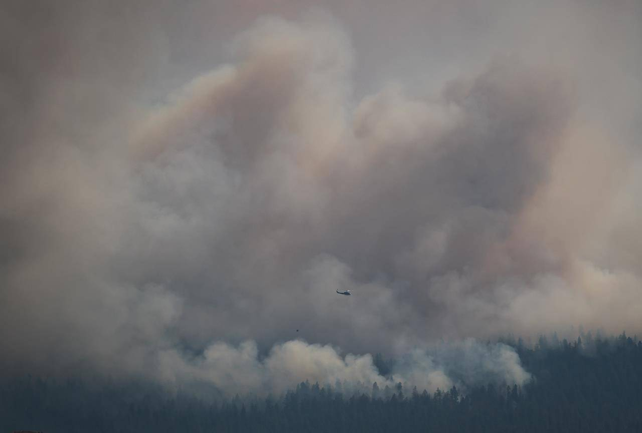 A helicopter with a water bucket flies past the Tremont Creek wildfire burning on the mountains above Ashcroft, B.C., on Friday, July 16, 2021. THE CANADIAN PRESS/Darryl Dyck