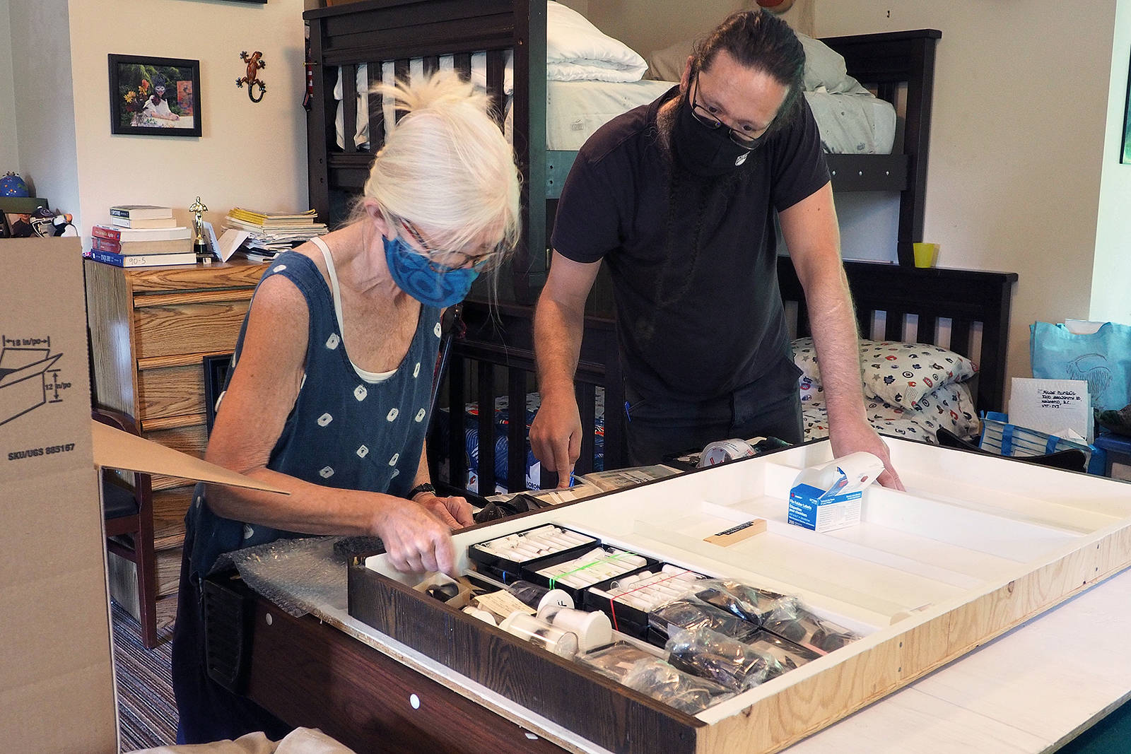 Sheila Byers, marine biologist and former interpreter for the Beaty Biodiversity Museum, and Colin MacLeod, zoologist with UBC's Biodiversity Research Centre and museum curatorial assistant, prepare Bill Merilees's mollusk shell collection for transport to Vancouver this past Tuesday, July 20. (Chris Bush/News Bulletin)