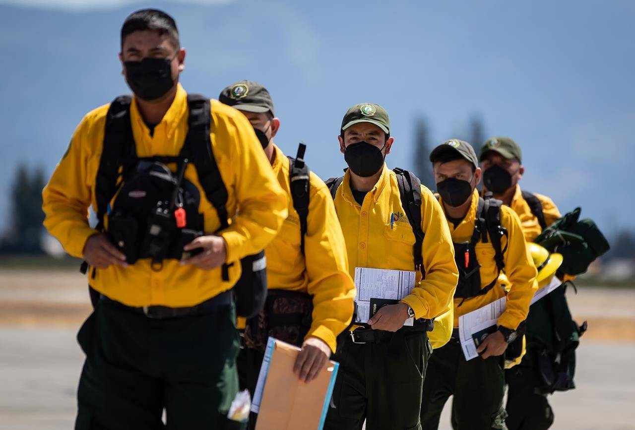 Firefighters from Mexico walk across the tarmac after arriving on a charter flight in Abbotsford, B.C, on Saturday, July 24, 2021. Ninety-nine firefighters will assist B.C. as the province deals with hundreds of wildfires burning in the province. THE CANADIAN PRESS/Darryl Dyck