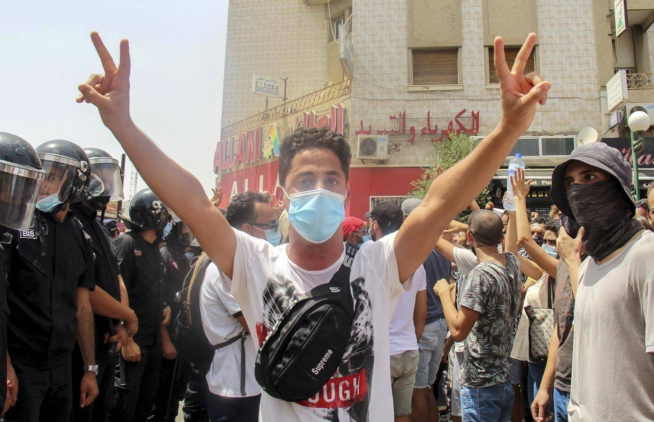 A demonstrator flashes victory sings as he faces Tunisian police officers during a demonstration in Tunis, Tunisia, Sunday, July 25, 2021. Violent demonstrations broke out on Sunday in several Tunisian cities as protesters expressed anger at the deterioration of the country's health, economic and social situation. (AP Photo/Hassene Dridi)