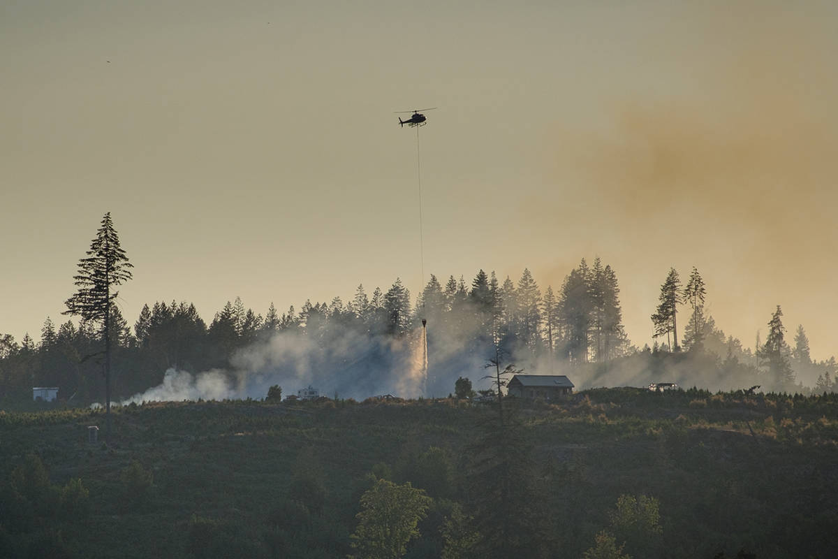 A helicopter drops water on a fire at Gogo's Christmas Tree Farm on Monday, July 26. (Photo courtesy Brian Irwin)
