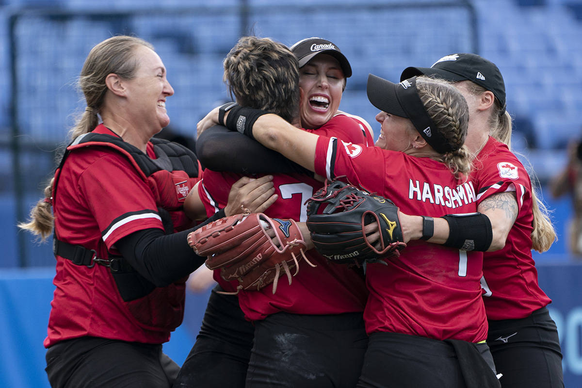 Canada's women's softball team players Kaleigh Rafter (left to right), Jenn Salling, Danielle Lawrie-Locke, Kelsey Harshman and Emma Entzminger celebrate their win over Mexico in the bronze medal game at the Tokyo Olympics in Yokohama, Japan. (THE CANADIAN PRESS/Adrian Wyld)