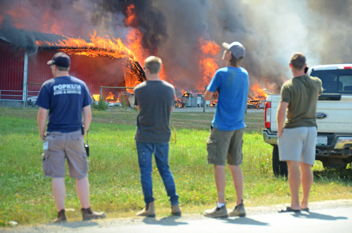 People watch as a chicken barn in Rosedale in Chilliwack burned to the ground in under an hour on July 27, 2021. (Paul Henderson/ Chilliwack Progress)