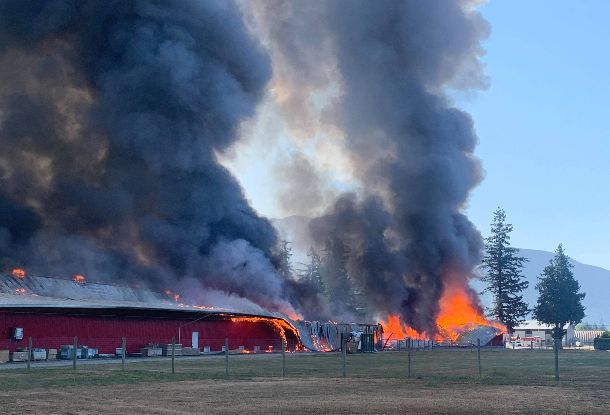 Smoke and flames can be seen billowing from a barn fire on Castleman Road in Chilliwack. (Paul Henderson/ Chilliwack Progress)