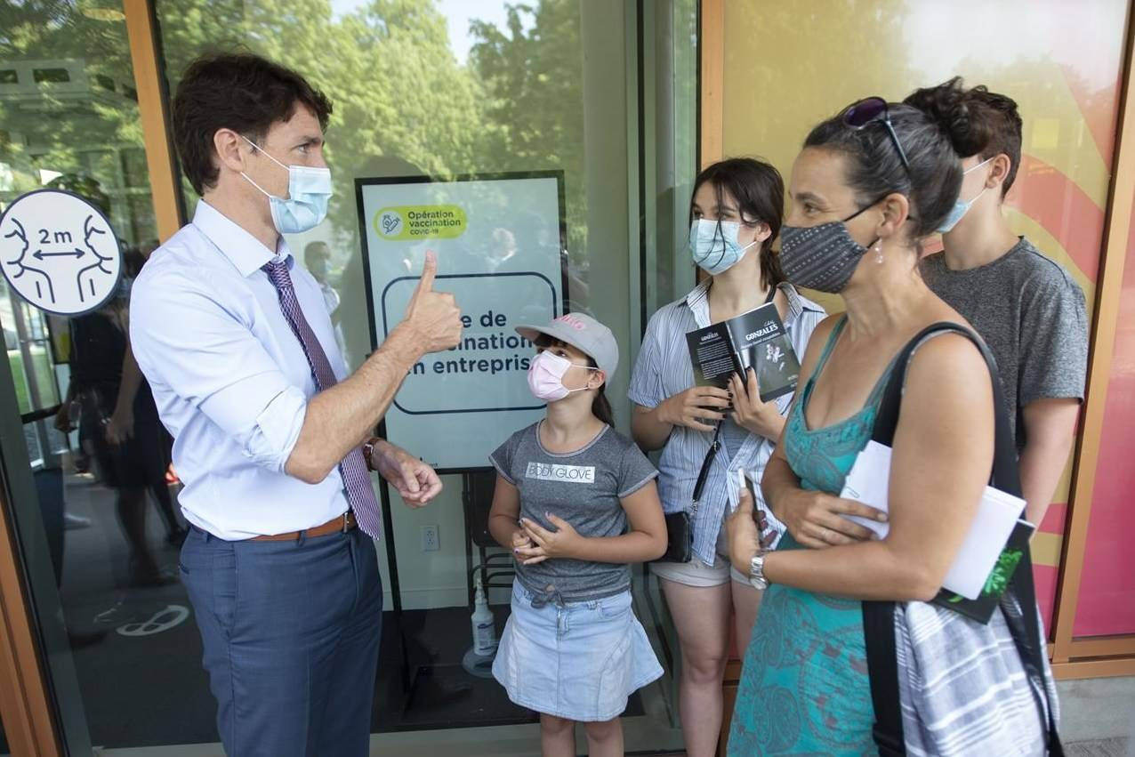 Prime Minister Justin Trudeau chats with people waiting for their shots while visiting a COVID-19 vaccination clinic, Thursday, July 15, 2021 in Montreal. Trudeau is urging Canadians who still have not gotten a COVID-19 vaccine to roll up their sleeves, saying that the overwhelming majority of cases are in people who haven't received their two shots.THE CANADIAN PRESS/Ryan Remiorz
