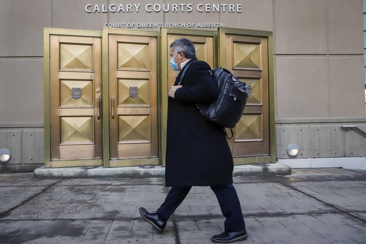 A man wears a mask as he enters the Calgary Courts Centre on Oct. 30, 2020, during the COVID-19 pandemic. Sentencing arguments for a Calgary pastor and his brother found guilty of contempt after deliberately violating COVID-19 health orders has been put over until September. THE CANADIAN PRESS/Jeff McIntosh
