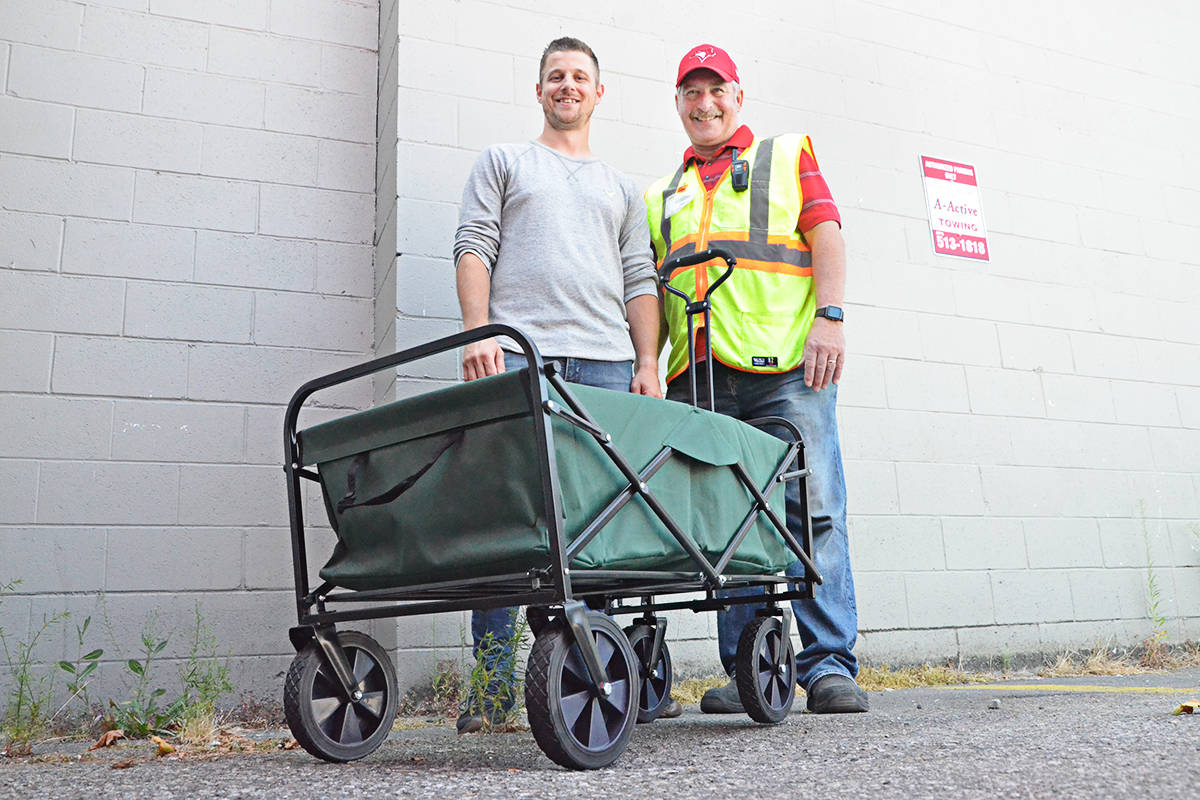 Pastor Jon Grochowski of SouthRidge Fellowship Church, and Jim Calamunce, executive director of the Langley Food Bank, with one of the new carts. (Matthew Claxton/Langley Advance Times)