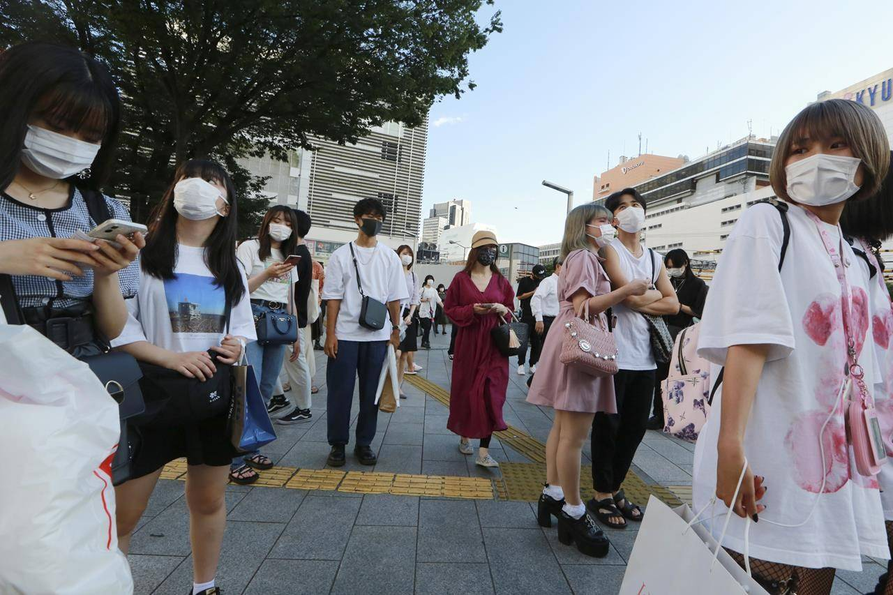 People wearing face masks to protect against the spread of the coronavirus walk on a street in Tokyo Tuesday, July 27, 2021. Tokyo reported its highest daily number of new coronavirus infections Tuesday, days after the Olympics began. (AP Photo/Koji Sasahara)