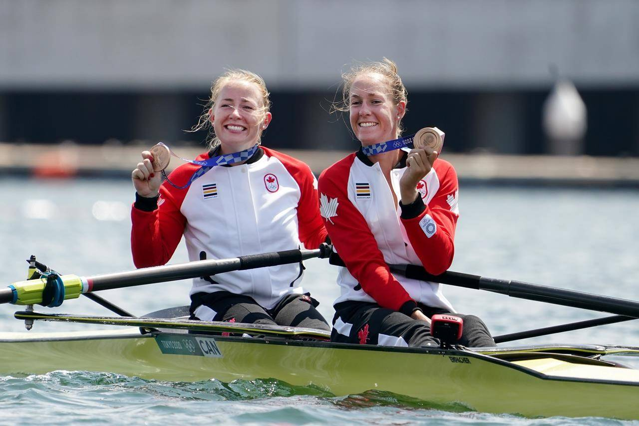 Canada's Caileigh Filmer (left) and Hillary Janssens show off their bronze medals, won in the women's pair rowing final event during the Tokyo Summer Olympic Games, in Tokyo, Thursday, July 29, 2021. THE CANADIAN PRESS/Nathan Denette