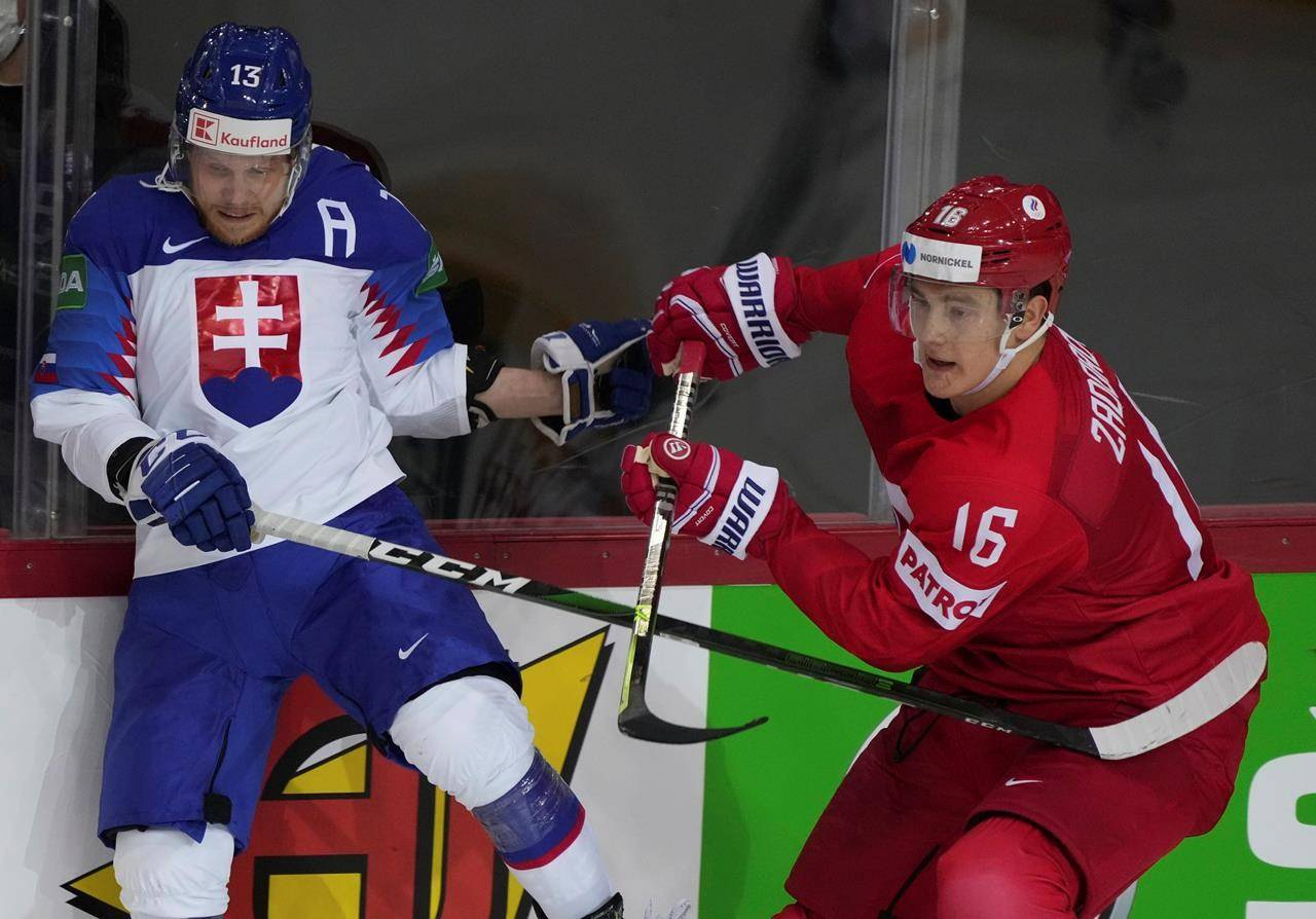 Michal Kristof of Slovakia, left, and Nikita Zadorov of Russia fight for a puck during the Ice Hockey World Championship group A match between the Slovakia and Russia at the Olympic Sports Center in Riga, Latvia, Monday, May 24, 2021. THE CANADIAN PRESS/AP-Roman Koksarov
