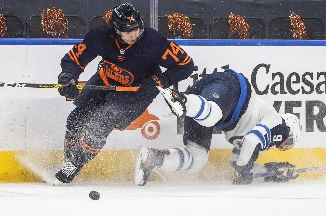Edmonton Oilers' Ethan Bear (74) checks Winnipeg Jets' Andrew Copp (9) during third period NHL playoff action in Edmonton on Wednesday, May 19, 2021.THE CANADIAN PRESS/Jason Franson
