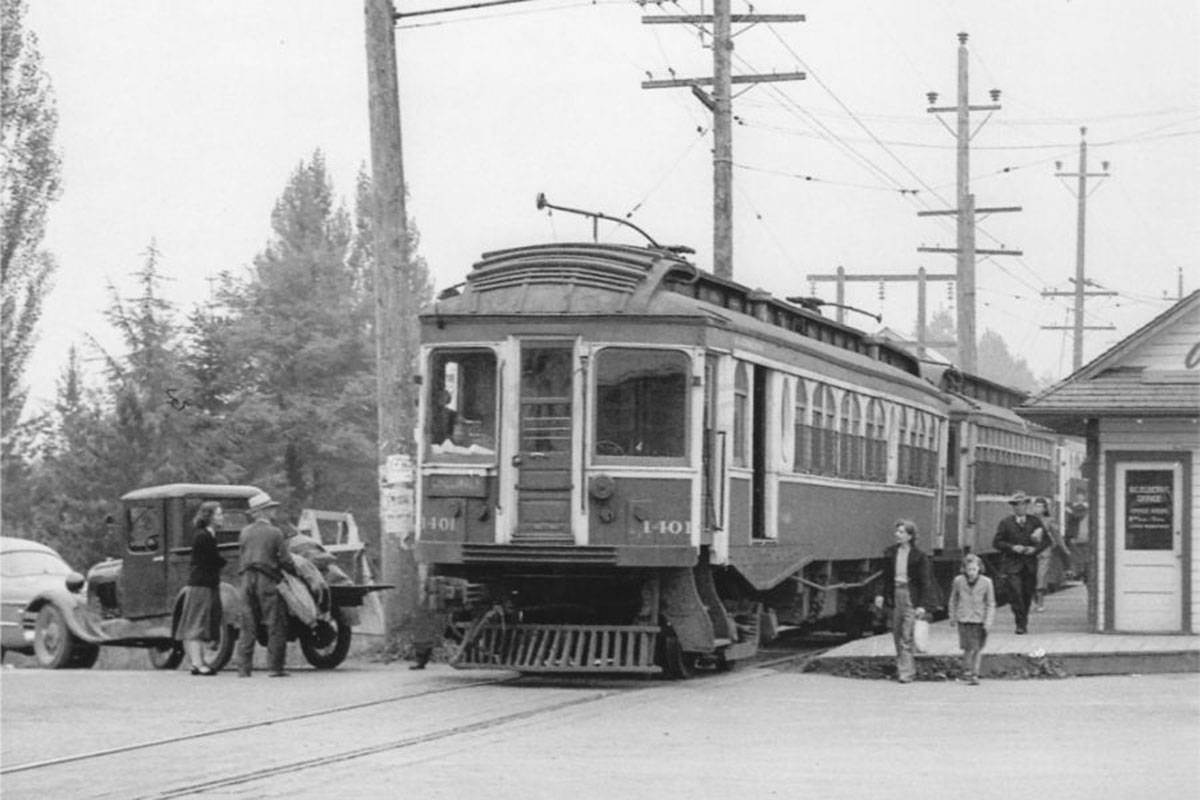 BCER Interurban Car 1401, an Ottawa Car Company built in 1910, has arrived at Langley Prairie Station  on its way to Chilliwack in late 1949, with St. Louis Car Company's 1913-built 1320 in tow as well as a BCER-built 1300 car with the conductor leaning out of vestibule door.  The station was re-built by July 1928 after a fire while the vehicle at the left (light colour) indicates a late 1940s model and a 1930s truck. Photo by Ernie Les Plant / BC Hydro - G.E. MacDonell Collection