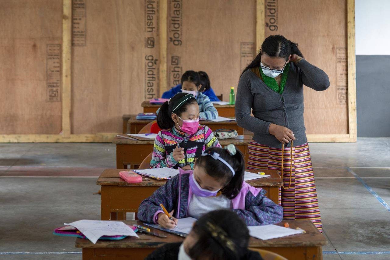 An exile Tibetan teacher invigilates as students write their half-yearly exams at the Tibetan Children's Village Day School in Dharmsala, India, Thursday, July 29, 2021. The students have been attending classes online but appeared for the exam in-person. (AP Photo/Ashwini Bhatia)