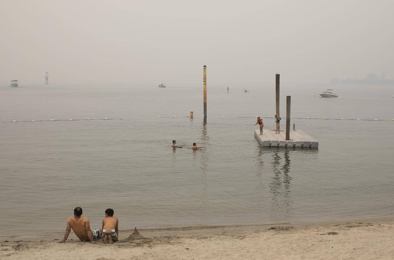 Wildfire smoke fills the air and obstructs the view of the mountains as people keep cool in Sicamous B.C., on Thursday July 29, 2021. THE CANADIAN PRESS/Jason Franson