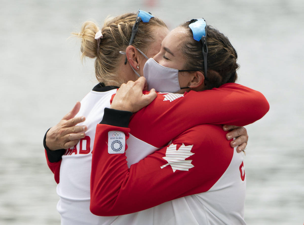 Canada's Christine Roper and Andrea Proske hug as they wait on the podium after winning the gold medal in women's eight rowing competition at the Tokyo Olympics, Friday, July 30, 2021 in Tokyo, Japan. (THE CANADIAN PRESS/Adrian Wyld)