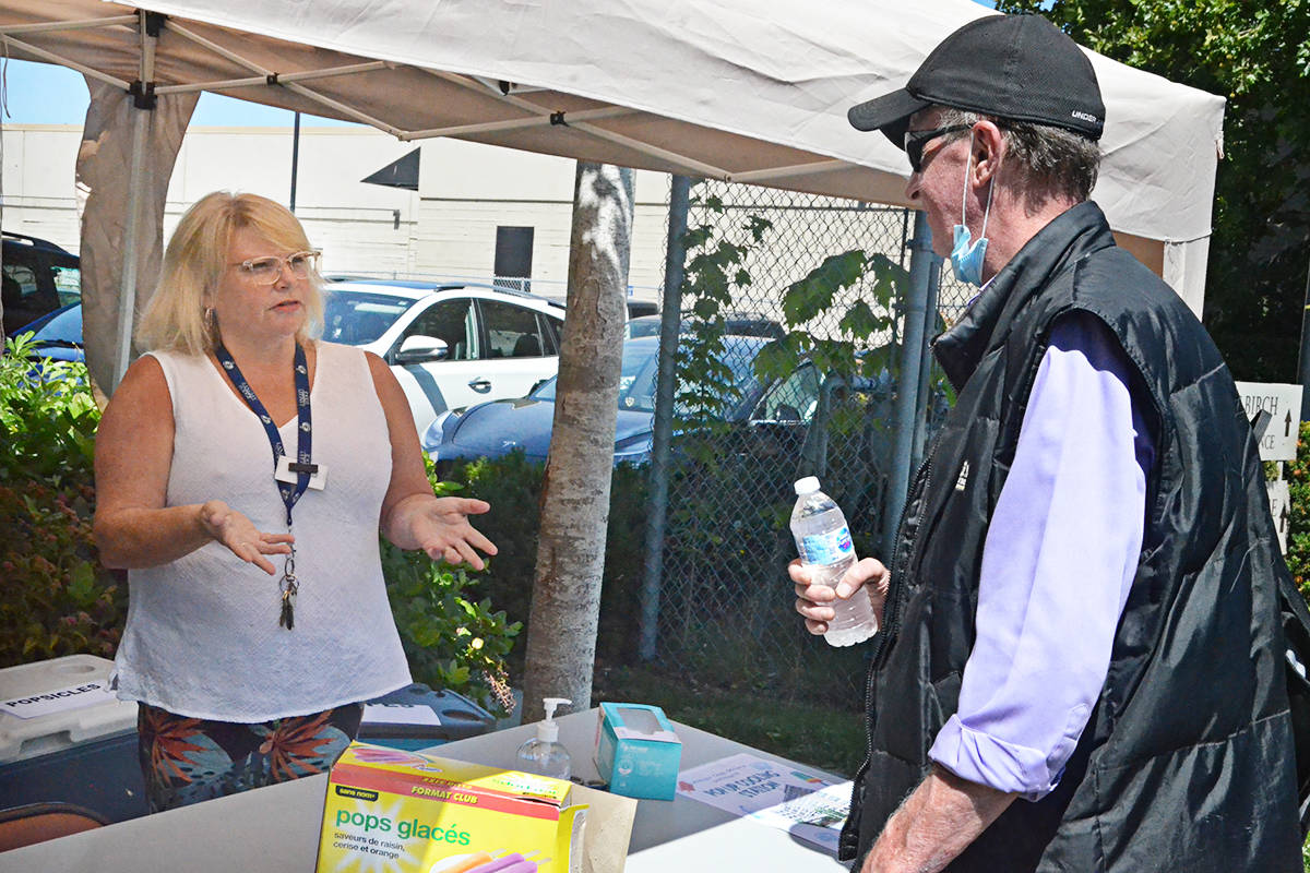 Lisa Samms-Maxwell of Langley Lodge spoke to Dave Hassett while handing out water and popsicles Friday during high temperatures. Langley Lodge was helping locals keep cool. (Matthew Claxton/Langley Advance Times)