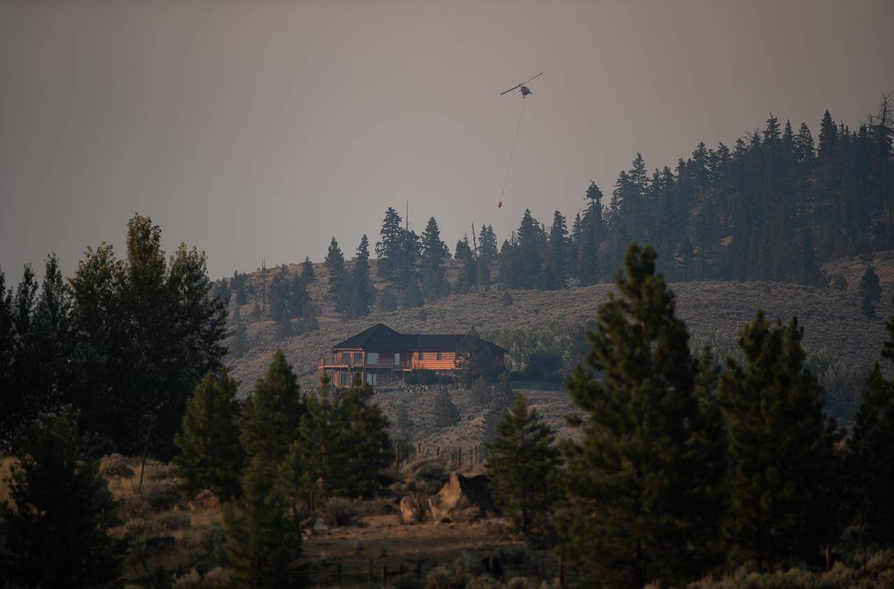 A helicopter carrying a bucket flies past a property at Barnes Lake while battling the Tremont Creek wildfire near Ashcroft, B.C., on Thursday, July 15, 2021. THE CANADIAN PRESS/Darryl Dyck
