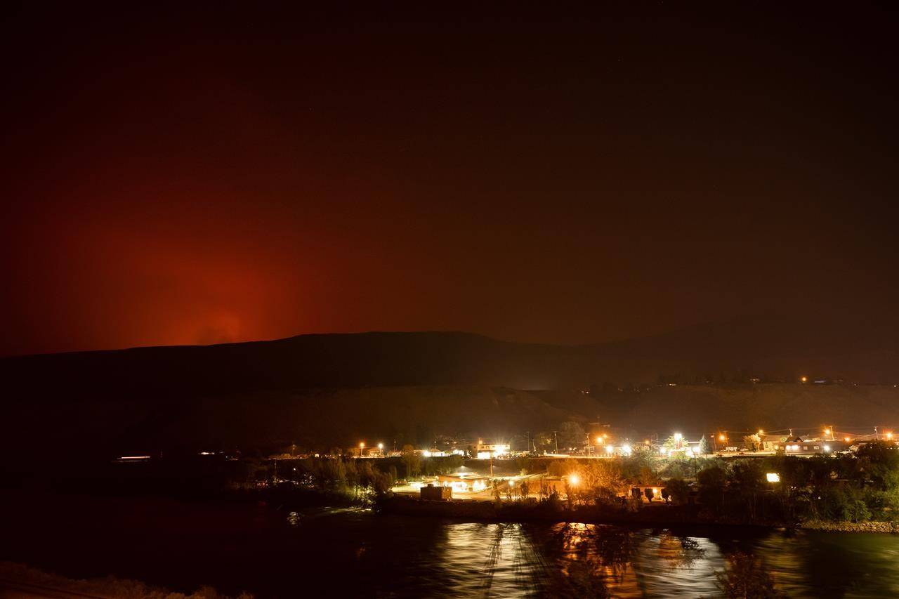 The sky glows orange as the Tremont Creek wildfire burns on a mountain in the distance above Ashcroft, B.C., on Thursday, July 15, 2021. THE CANADIAN PRESS/Darryl Dyck.