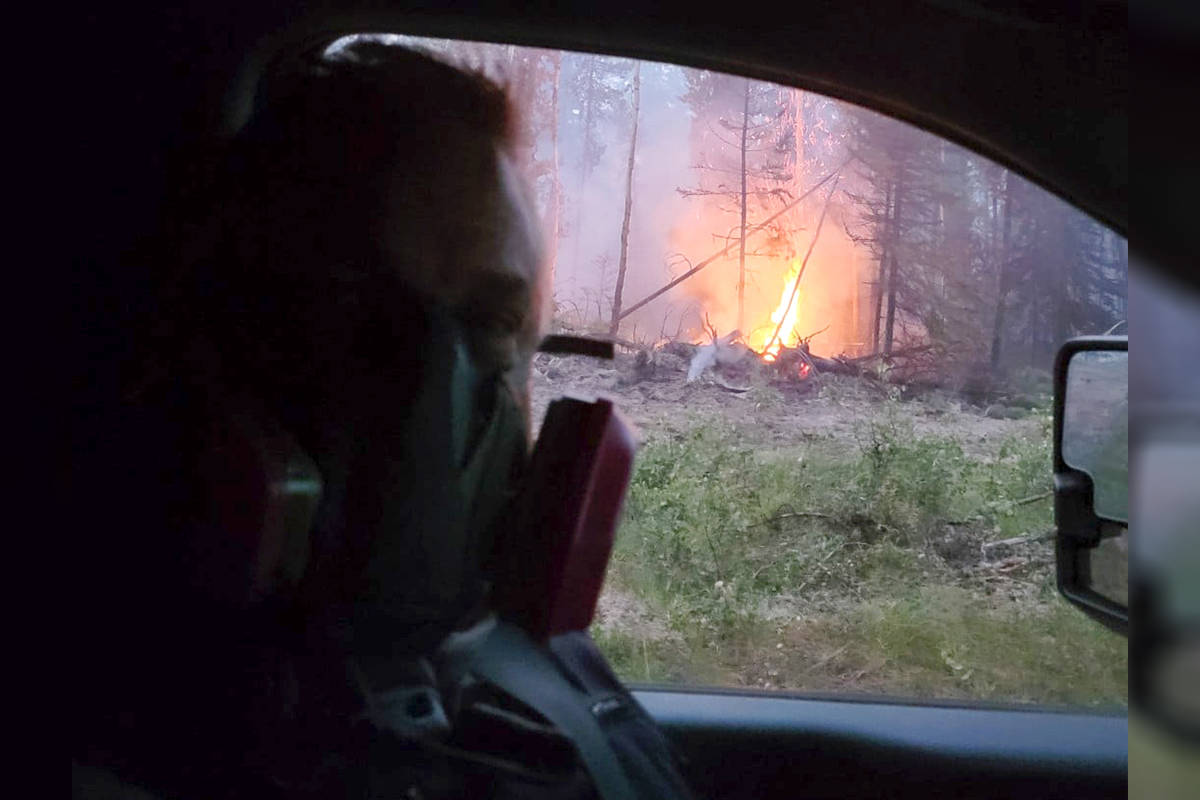 """Mounties with Langley RCMP provided support to policing services in 100 Mile House. """"Our Langley members helping out with the wildfire and keeping the community safe,"""" the detachment captioned this photo posted July 21, 2021. (Langley RCMP Detachment/Facebook)"""