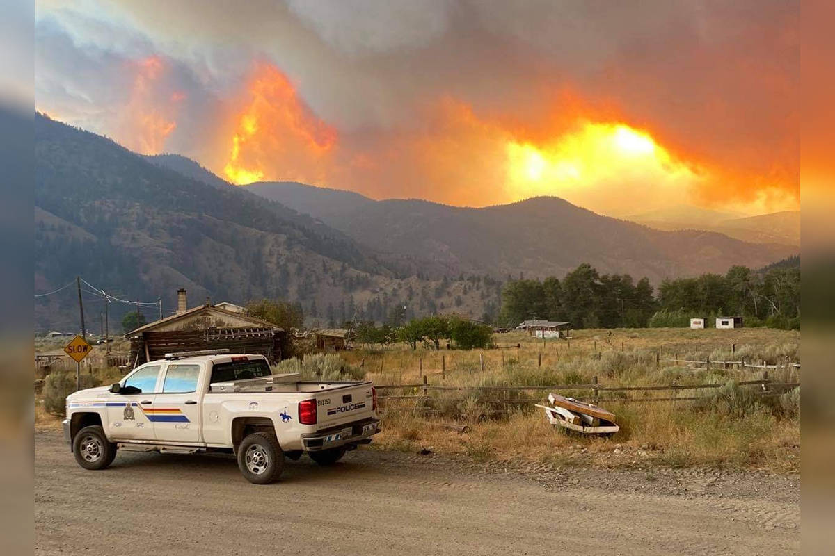 """Mounties with Langley RCMP provided support to policing services in 100 Mile House. """"Currently in 100 Mile House - our members are continuing to assist against the B.C. wildfires,"""" the detachment captioned this photo posted July 23, 2021. (Langley RCMP Detachment/Facebook)"""