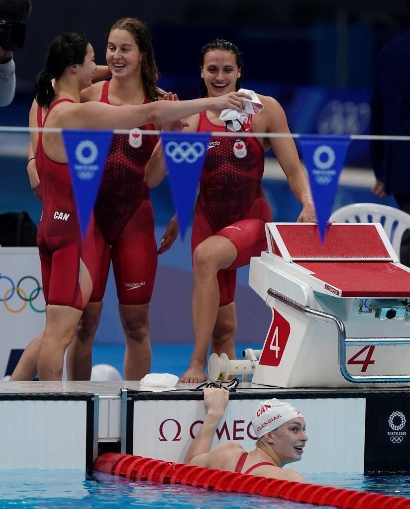 Canada's Maggie Mac Neil, left to right, Sydney Pickrem, Kylie Masse and Penny Oleksiak, in the water, celebrate a bronze medal in the women's 4 x 100m medley relay final during the Tokyo Summer Olympic Games, in Tokyo, Sunday, August 1, 2021. THE CANADIAN PRESS/Adrian Wyld