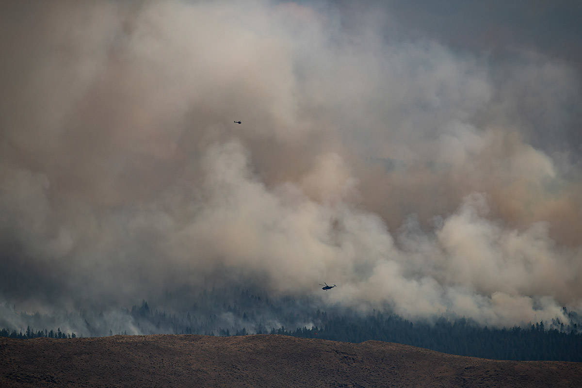 Helicopters fly past the Tremont Creek wildfire as it burns on the mountains above Ashcroft, B.C., on Friday, July 16, 2021. THE CANADIAN PRESS/Darryl Dyck