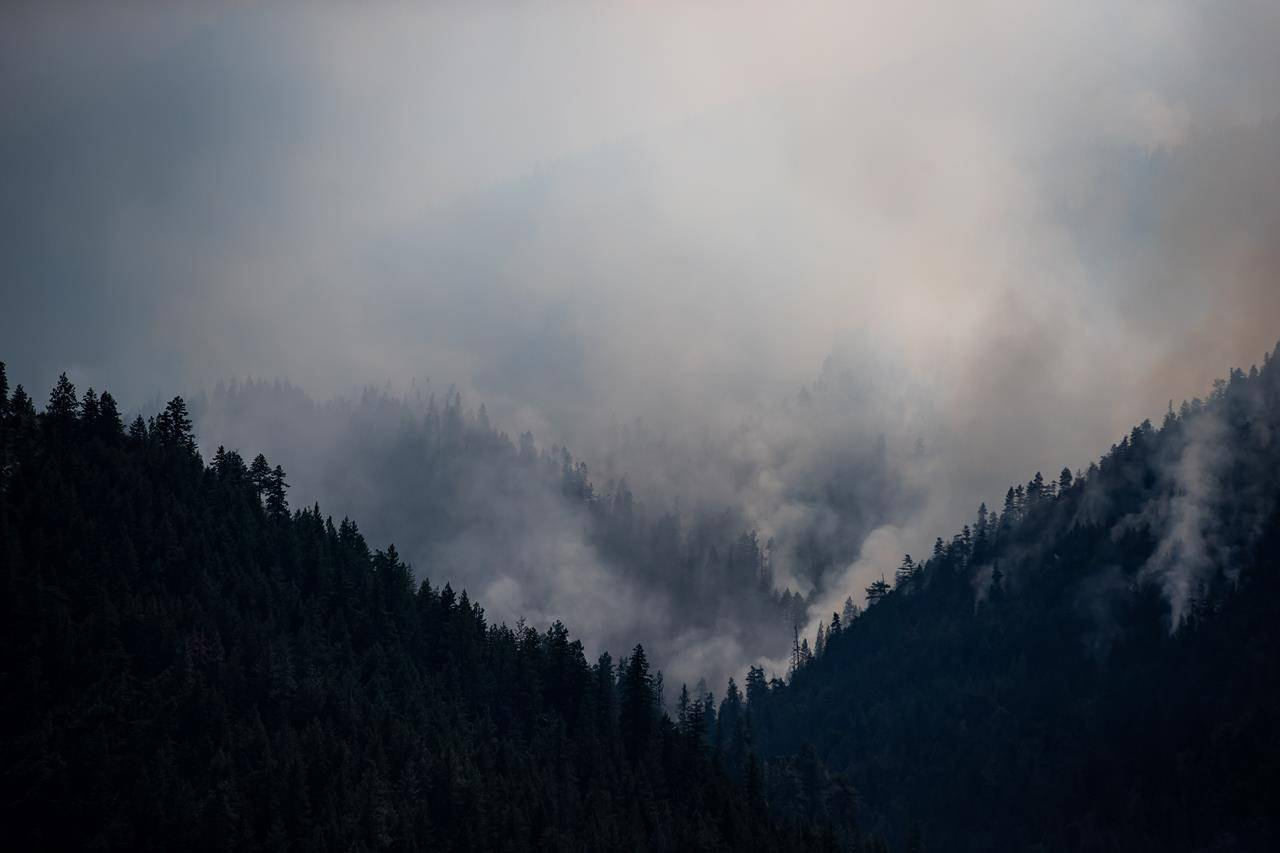 A wildfire burns on a mountain above the Trans-Canada Highway near Lytton, B.C., on Friday, July 9, 2021. British Columbia is reporting a slight increase in the number of active wildfires but cooler temperatures and forecasts of rain ahead could bring some relief. THE CANADIAN PRESS/Darryl Dyck