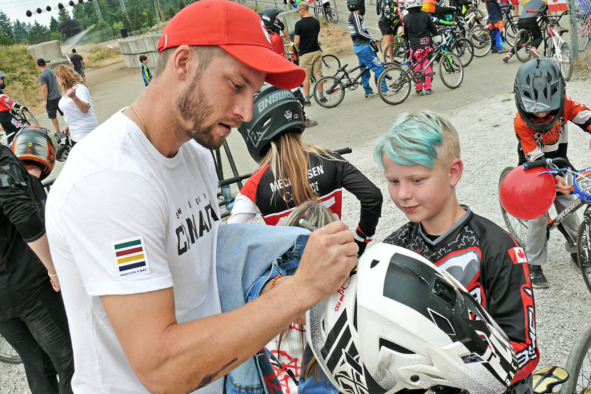 Fellow BMX Olympian James Palmer signed a young rider's helmet at the Langley BMX track on Sunday, Aug.1, which staged a surprise welcome-back for fellow Olympian and Langley rider Drew Mechielsen. (Dan Ferguson/Langley Advance Times)