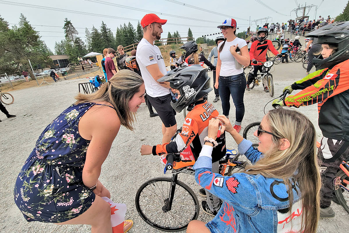 Drew Mechielsen (R) signed a young fan's jersey at the Langley BMX track on Sunday, Aug. 1, her first day back from Tokyo where she rode into the finals. (Dan Ferguson/Langley Advance Times)