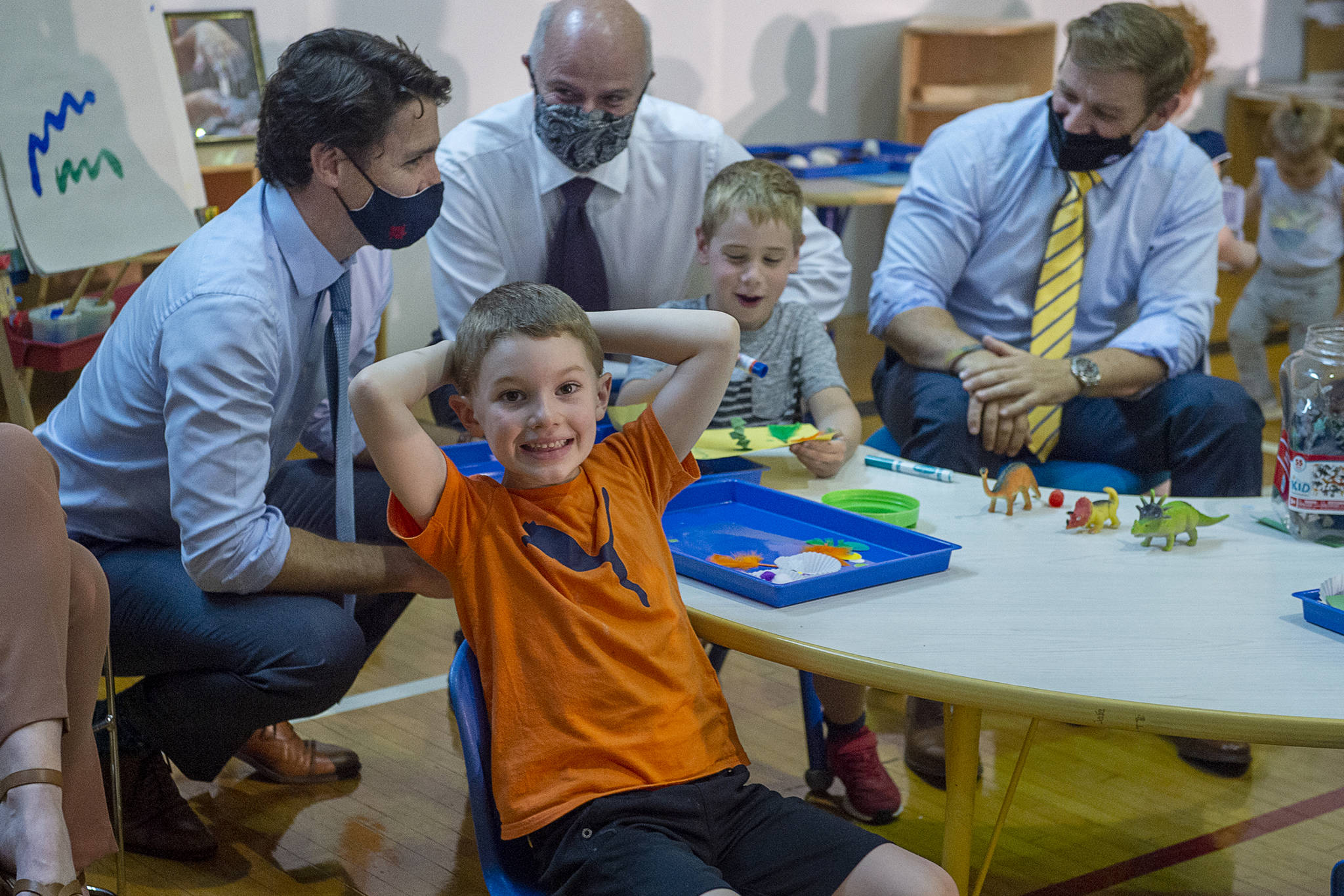 A young boys smiles for the cameras as Prime Minister Justin Trudeau, Education Minister Tom Osborne and Newfoundland and Labrador Premier Andrew Furey, left to right, engage with children at the College of the North Atlantic in St. John's, N.L. on Wednesday, July 28, 2021. The province has struck a deal with Ottawa for a $10-a-day child-care program. THE CANADIAN PRESS/Andrew Vaughan