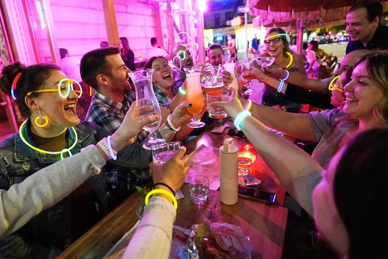 """FILE — In this May 17, 2021 file photo, Emily Baumgartner, left, and Luke Finley, second from left, join friends from their church group in a birthday toast to one of the members, upper right, during their weekly """"Monday Night Hang"""" gathering at the Tiki Bar on Manhattan's Upper West Side, in New York. New York Gov. Andrew Cuomo and New York City Mayor Bill de Blasio have scheduled competing news conferences Monday, Aug. 2 amid rising COVID-19 case counts attributed to the highly contagious delta variant of the virus. (AP Photo/Kathy Willens, File)"""