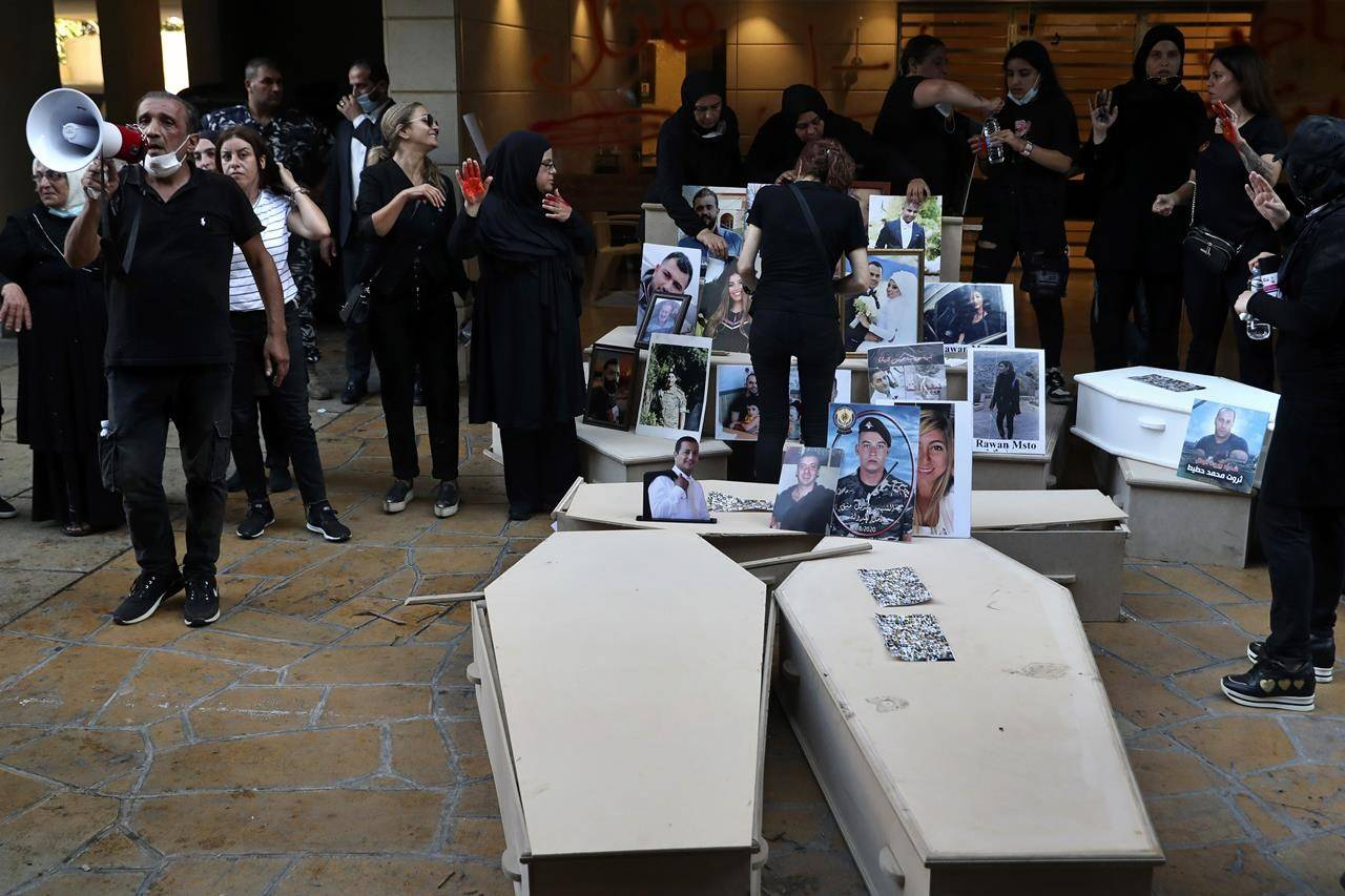 Ibrahim Hoteit, 51, left, the brother of Tharwat Hoteit, who was killed in last year's massive blast at Beirut's seaport, leads a chant as relatives of others who were killed, stand next to empty coffins with portraits of the dead, during a protest outside the home of caretaker Interior Minister Mohamed Fehmi, in Beirut, Lebanon, Tuesday, July 13, 2021. A year after the deadly blast, families of the victims are consumed with winning justice for their loved ones and punishing Lebanon's political elite, blamed for causing the disaster through their corruption and neglect. (AP Photo/Bilal Hussein)