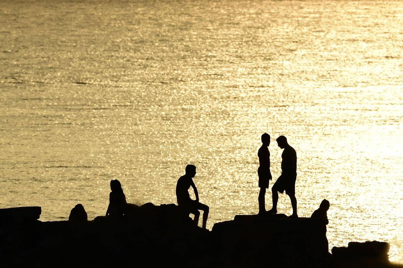People stand on rocks near a beach of Kavouri suburb, southwest of Athens, Greece, Monday, Aug. 2, 2021. The heat wave is expected to peak Monday, with temperatures inland ranging from 42 to 46 degrees Celsius (107.6 to 114.8 Fahrenheit). Temperatures will remain at 40 Celsius (104 Fahrenheit) or above in much of Greece until at least Friday, meteorologists say. (AP Photo/Michael Varaklas)