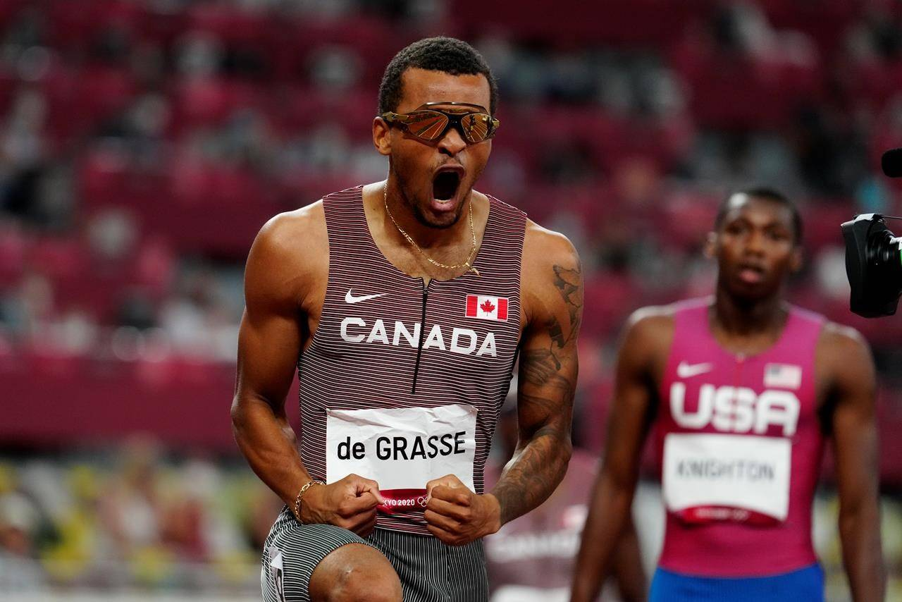 Canada's Andre De Grasse reacts after racing to a gold medal as American Erriyon Knighton looks on in the Men's 200m final during the Tokyo Olympics in Tokyo, Japan on Wednesday, August 4, 2021. After two days without any medals at the Tokyo Olympics, Andre De Grasse got Canada back on the board with the greatest run of his stellar career. THE CANADIAN PRESS/Frank Gunn