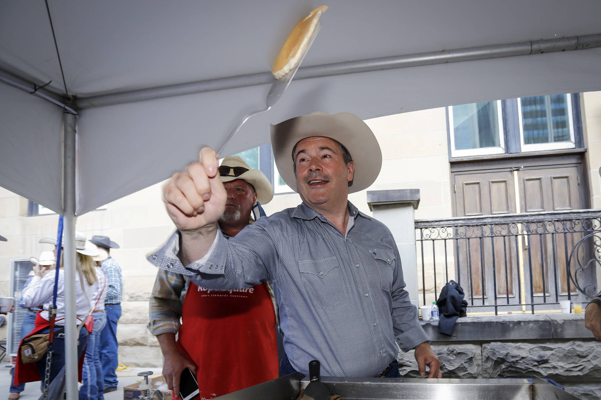 Alberta Premier Jason Kenney, right, cooks pancakes while hosting the Premier's annual Stampede breakfast in Calgary, Alta., Monday, July 12, 2021.THE CANADIAN PRESS/Jeff McIntosh