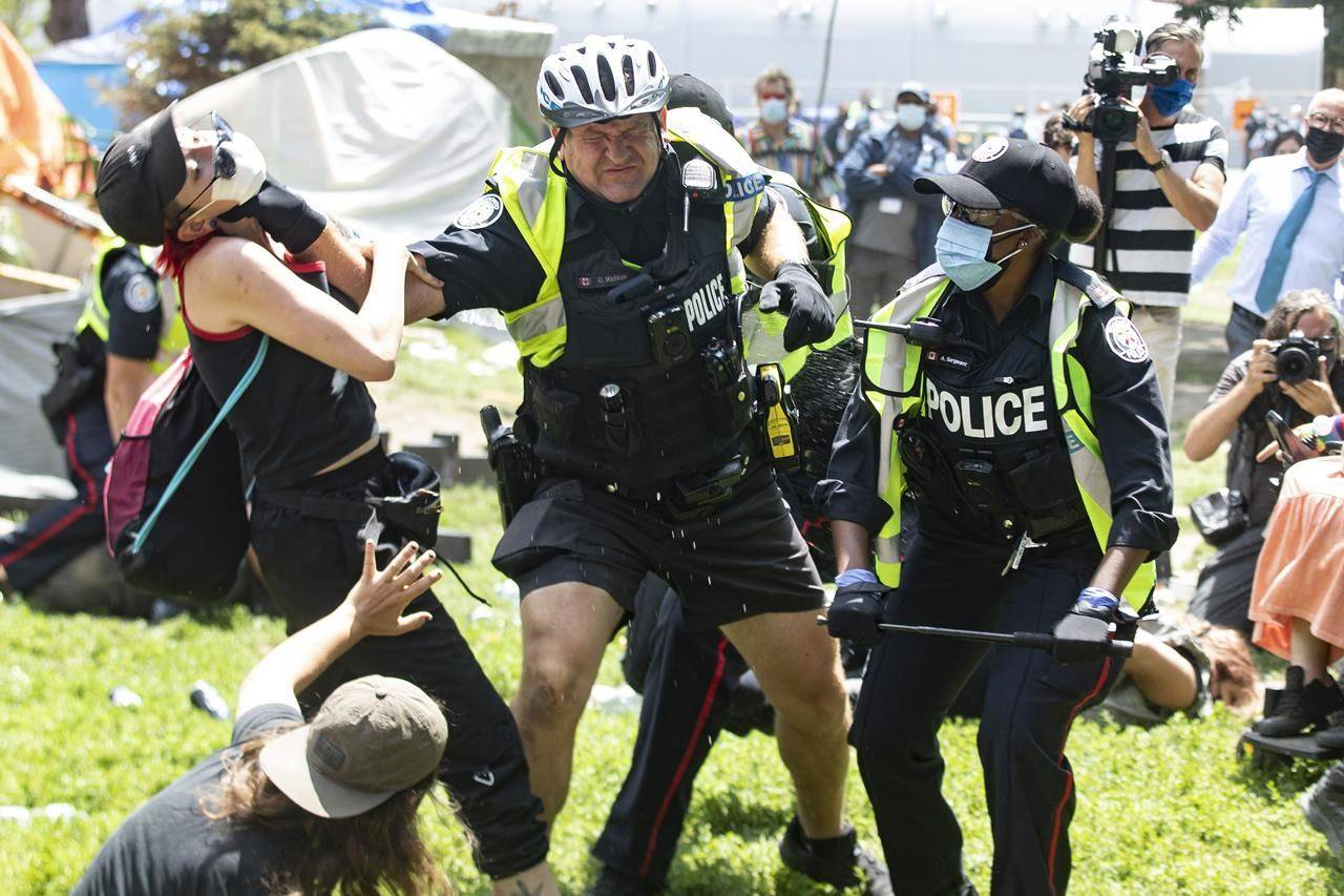 Police remove encampment supporters as they clear Lamport Stadium Park encampment in Toronto, Wednesday, July 21, 2021. Police and politicians' efforts to limit public access to recent events in Toronto and Vancouver Island have cast a spotlight on the role of journalists and spurred concerns over freedom of the press. THE CANADIAN PRESS/Chris Young