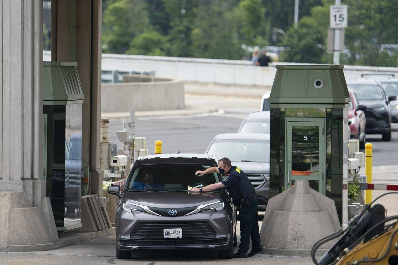 A CBSA officer places a document on the windshield of a car entering Canada and asks it to pull off to the side in Niagara Falls, Ont., Friday, July 16, 2021. A union representing about 9,000 Canadian Border Service Agency workers says its members will begin job action across the country on Friday. THE CANADIAN PRESS/Peter Power