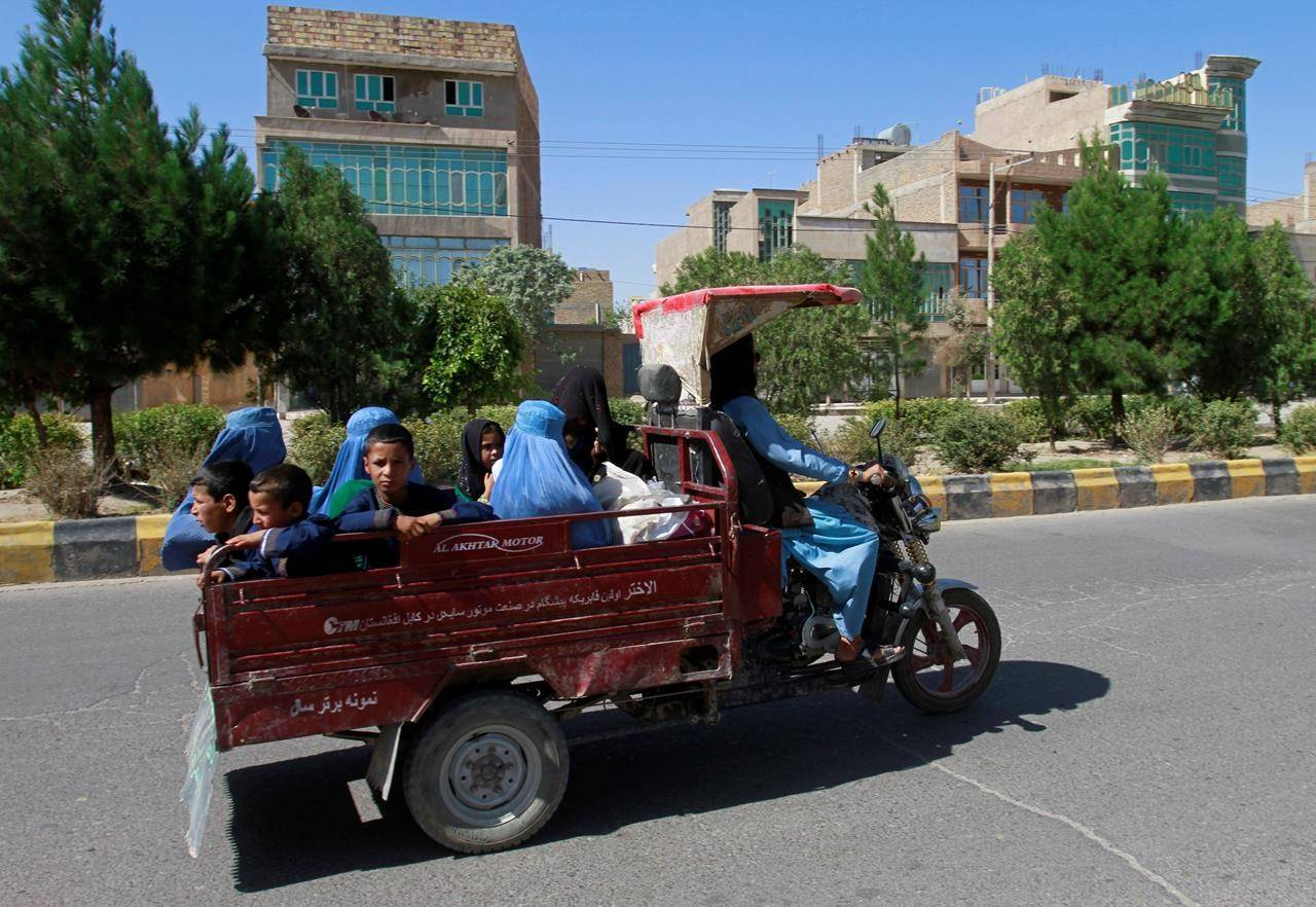 Afghan women and children travel in a motorcycle cart during fighting between Taliban and Afghan security forces in Herat province, west of Kabul, Afghanistan, Sunday, Aug. 1, 2021. The first planeload of Afghan refugees who supported the Canadian military mission in Afghanistan has arrived in Canada. THE CANADIAN PRESS/AP-Hamed Sarfarazi