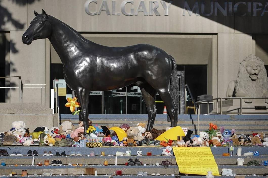 A growing memorial, in honour of the 215 residential school children whose remains have been discovered buried near the former residential school in Kamloops, B.C., sits outside Calgary City Hall in Calgary, Alta., Wednesday, June 2, 2021. Calgary police say they are investigating an arson at the memorial. THE CANADIAN PRESS/Jeff McIntosh