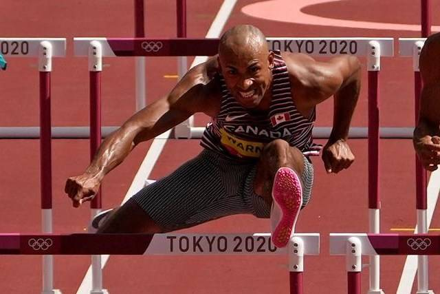 Damian Warner of Canada clears a hurdle alongside Garrett Scantling, of United States in a heat of the decathlon men's 110-metre hurdles at the 2020 Summer Olympics, Thursday, Aug. 5, 2021, in Tokyo, Japan. THE CANADIAN PRESS/AP-Charlie Riedel