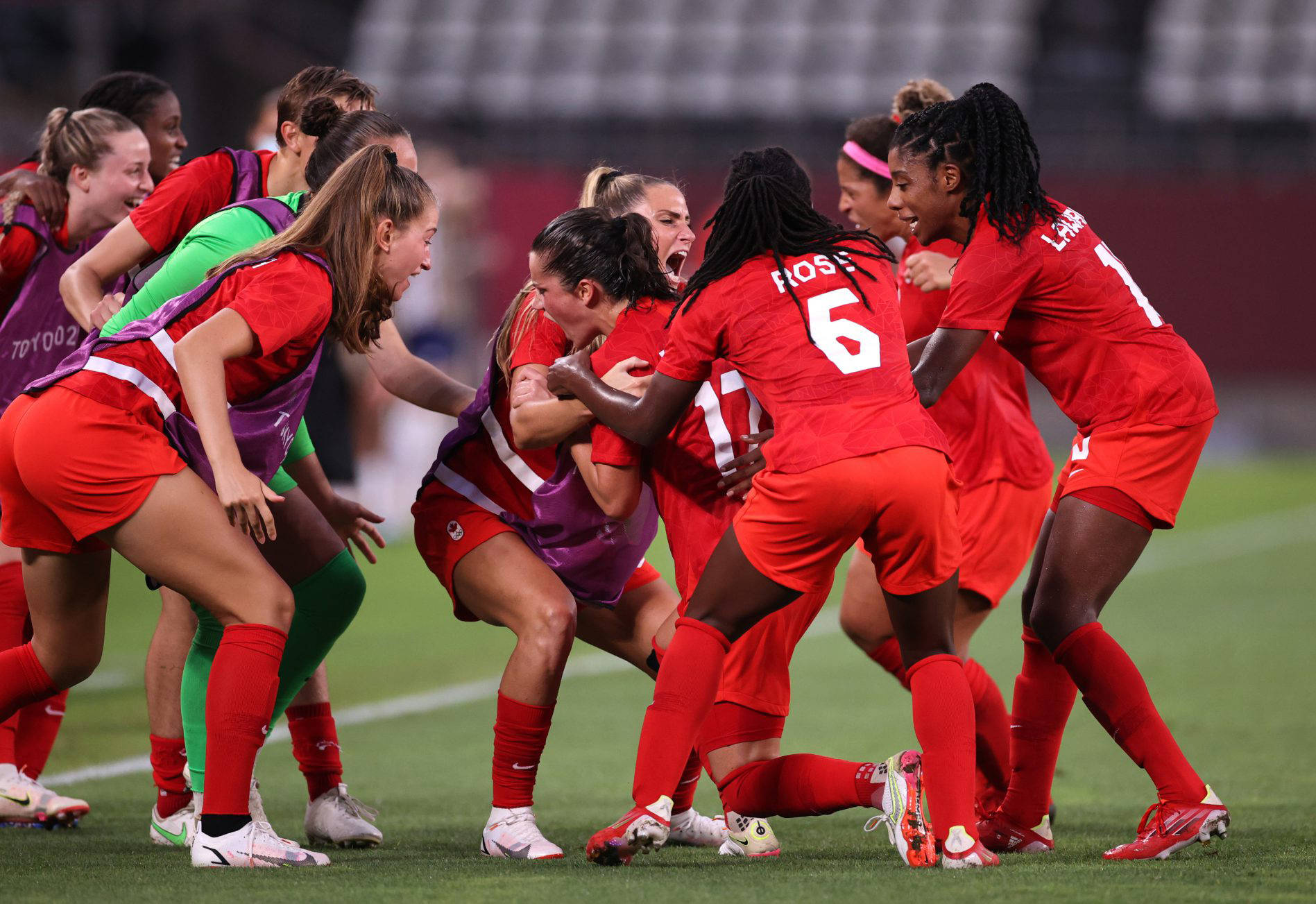 Chilliwack's Jordyn Huitema (left in red jersey/shorts with purple pinnie) joins Canadian national women's soccer squad teammates mobbing Jessie Fleming after her penalty kick goal lifted the team to a 1-0 semi-final win over the United States. (Canada Soccer photo)