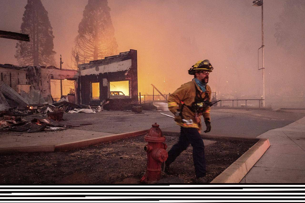 A firefighter battles the Dixie Fire as it tears through the Greenville community in Plumas County, Calif., Wednesday, Aug. 4, 2021. The fire leveled multiple historic buildings and dozens of homes in central Greenville. (AP Photo/Noah Berger)