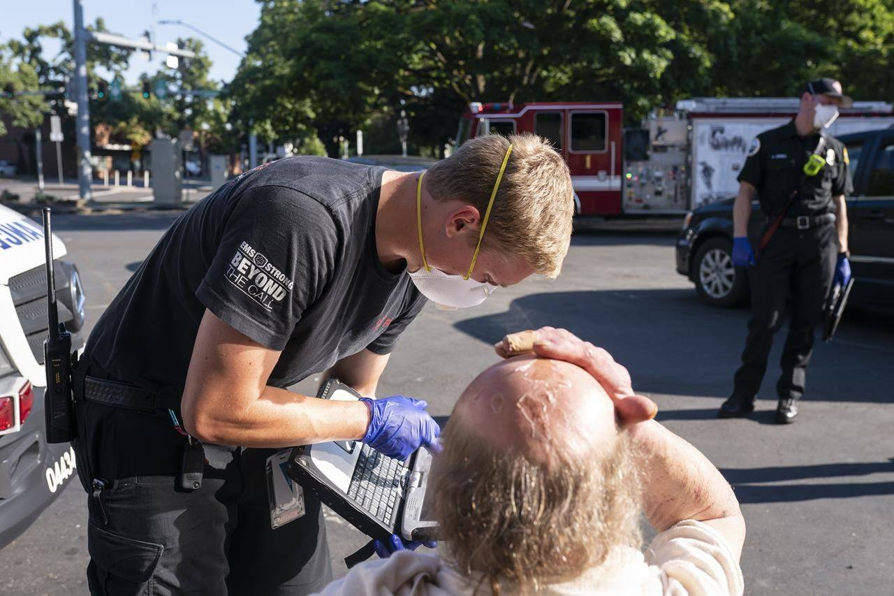FILE- In this Saturday, June 26, 2021 file photo a paramedic with Falck Northwest ambulances treats a man experiencing heat exposure during a heat wave, in Salem, Ore. Consecutive days of temperatures as high as 116 F in Portland, Ore., made a folly of years of planning for more anticipated emergencies such as earthquakes and snowstorms and it was only as the disaster unfolded that authorities got a sense of how devastating it would ultimately be. (AP Photo/Nathan Howard,File)
