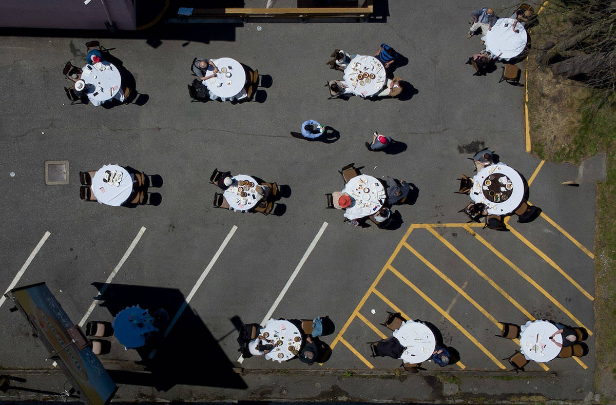 People eat lunch in the parking lot outside the Pink Pearl Chinese restaurant, in Vancouver, on Tuesday, May 25, 2021. The British Columbia government has introduced a four-step restart plan in a gradual return to normality when more people are vaccinated against COVID-19. THE CANADIAN PRESS/Darryl Dyck