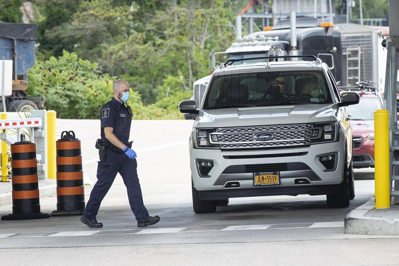 A Canada Border Services Agency agent wears a mask at the Thousand Islands US/Canada border crossing in Lansdowne, Ont., on Friday July. 30, 2021. A group of U.S. and Canadian business leaders is pushing Congress for a plan to ease restrictions at the land border with Canada. THE CANADIAN PRESS/Lars Hagberg