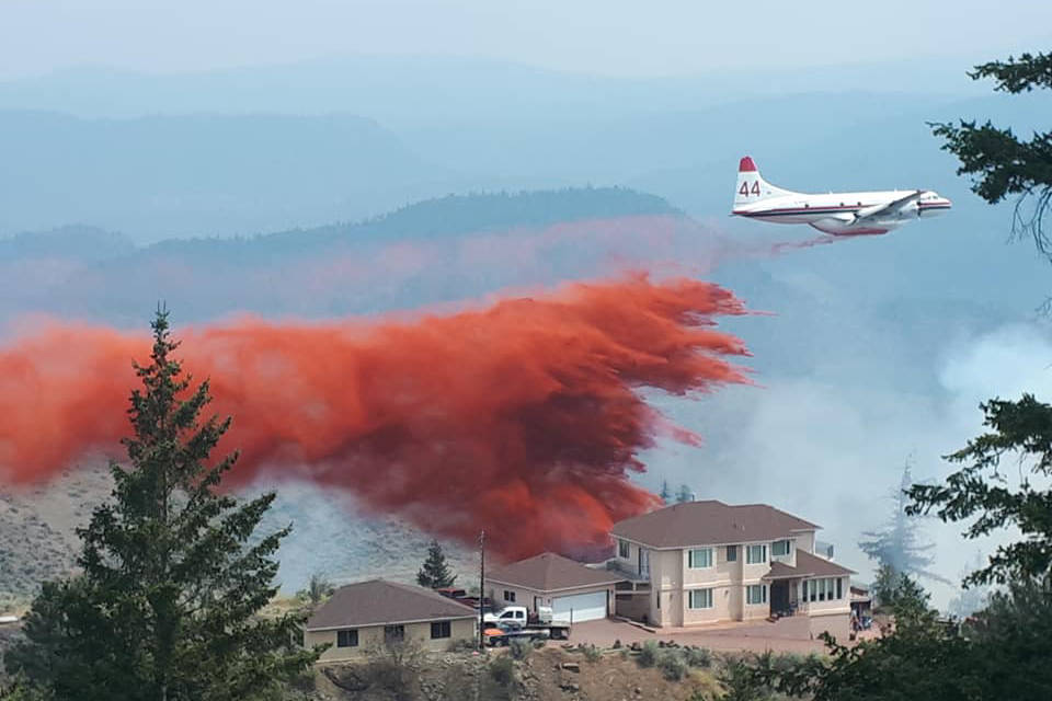 Air bombers drop fire retardant with precise accuracy to protect a home dangerously close to the Osoyoos wildfire that started up off Highway 3 Monday morning, July 5, 2021. (Sam Tibbitt photo Facebook)