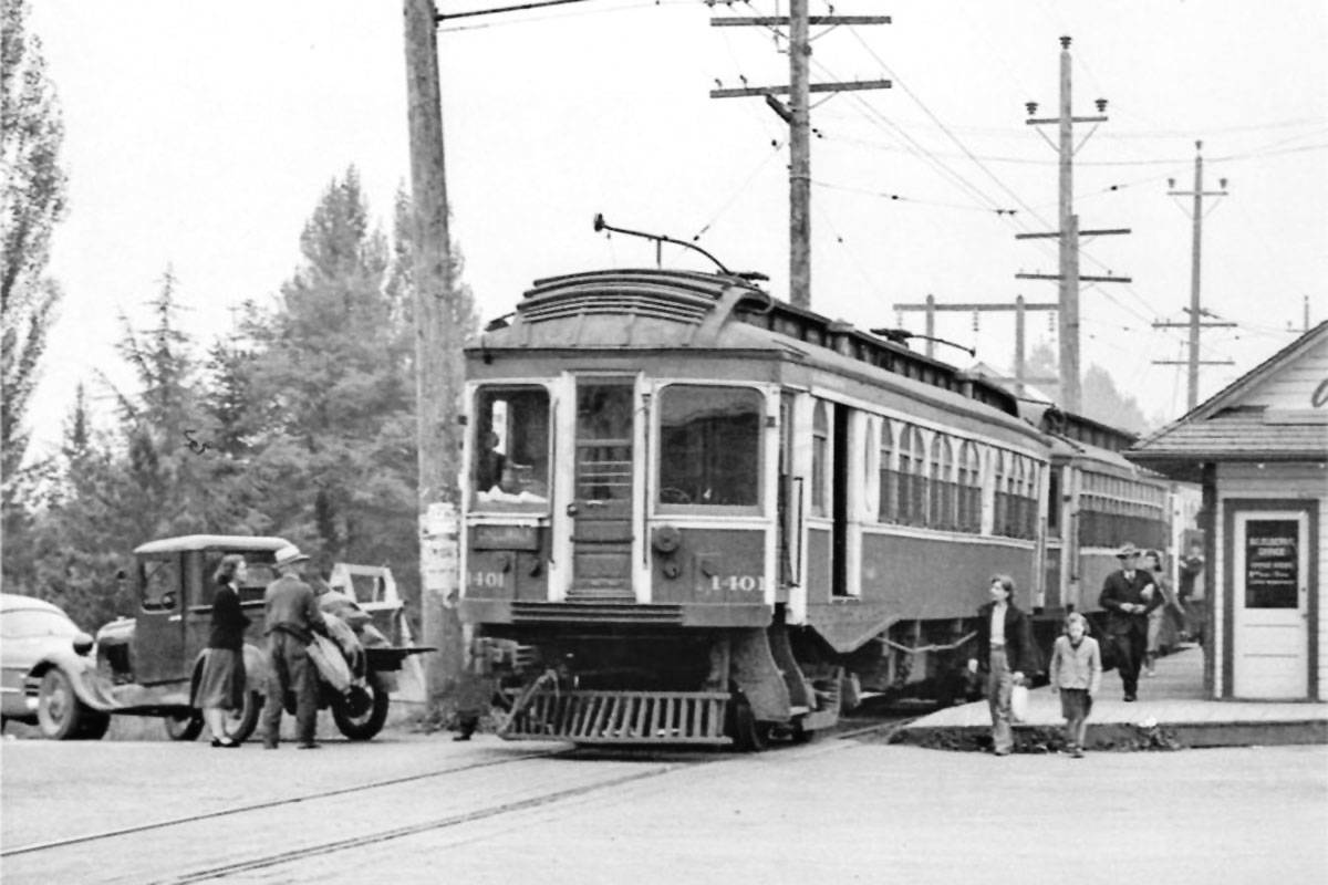 BCER Interurban Car 1401, an Ottawa Car Company built in 1910, has arrived at Langley Prairie Station on its way to Chilliwack in late 1949, with St. Louis Car Company's 1913-built 1320 in tow as well as a BCER-built 1300 car with the conductor leaning out of vestibule door. The station was re-built by July 1928 after a fire while the vehicle at the left (light colour) indicates a late 1940s model and a 1930s truck. (Ernie Les Plant/BC Hydro – G.E. MacDonell Collection)