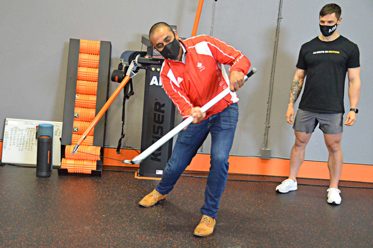 Jobs minister Ravi Kahlon tried out his slapshot on a piece of exercise equipment at AIM Athletic in Langley on Friday. Kahlon announced more money for thousands of B.C. business owners to learn about digital marketing. (Matthew Claxton/Langley Advance Times)