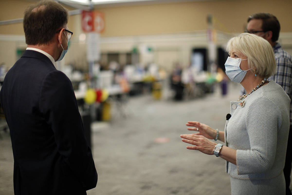 Provincial health officer Dr. Bonnie Henry is joined by Minister of Health Adrian Dix at the Victoria Conference Centre vaccination site to promote walk-in Wednesdays, an effort by the province to encourage those needing a first or second dose of the COVID-19 vaccine during a site tour in Victoria, B.C., on Tuesday, August 3, 2021. THE CANADIAN PRESS/Chad Hipolito